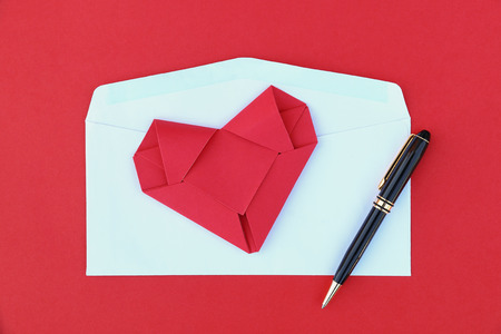 it is folding red paper heart on white envelope and black business pen. Stock Photo