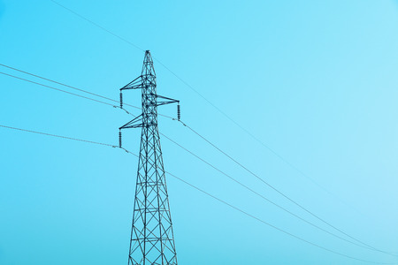 it is high voltage electricity post with cables and blue sky.