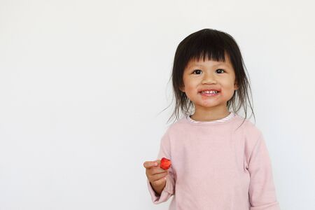 smiling asian girl enjoys eating red strawberry and having dirty face.