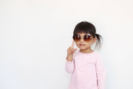 happy asian girl wears sunglasses and point in the air. 免版税图像