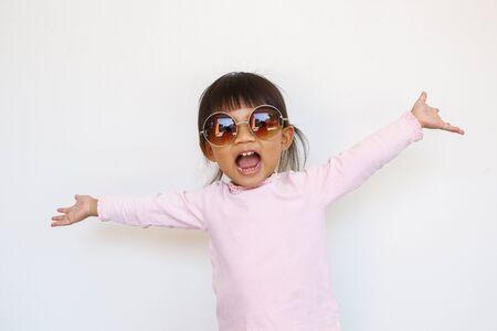 one cheerful asian kid wears dark sunglasses.