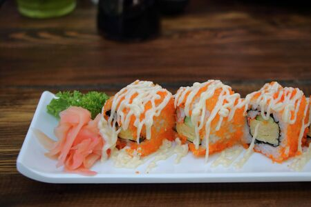 california rolls with dressing on white plate.