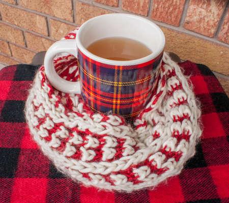 fuzzy: Plaid winter mug wrapped in fuzzy knit winter scarf. Stock Photo