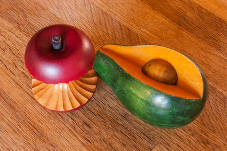 hard core: Wooden apple and avocado on display on a butcher block cutting board Stock Photo