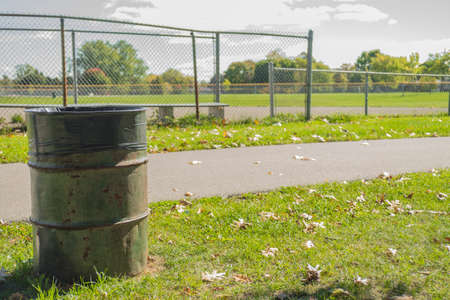baseball stuff: Garbage can in front of baseball field