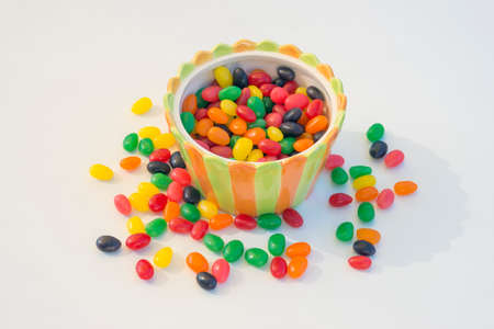 jelly beans: Multicolored jelly beans in a vibrant striped candy bowl