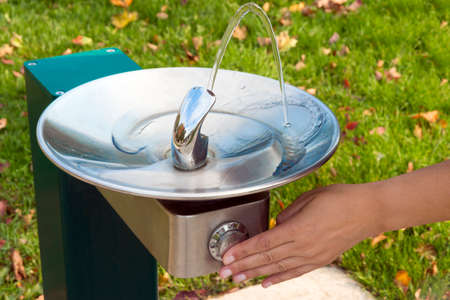 revive: Hand pressing park fountain button, causing water to flow for a cool drink