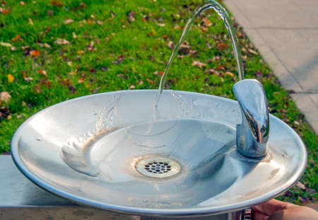 Park water fountain turned on with water flowing down Stock Photo