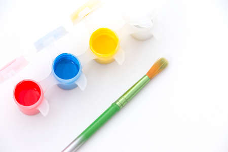 vibrant paintbrush: Paint pots with vibrant red, yellow, blue and white paint, alongside a green paintbrush