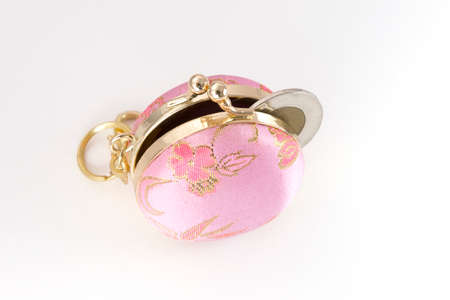 slightly: Tiny pink and gold change purse slightly open with coin sticking out