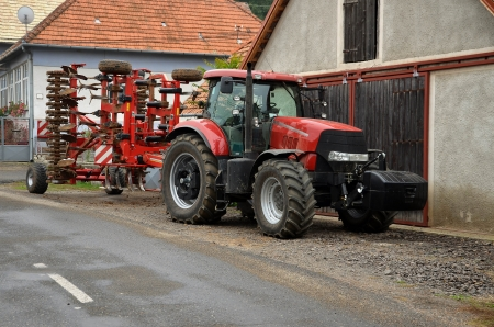 agro: Red tractor with agro cultivator in the village Stock Photo