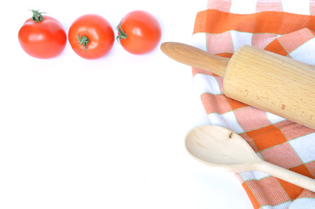 dishcloth: Checkered dishcloth, spoon, tomatoes and rolling pin isolated on white