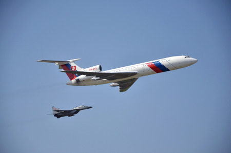 escorted: Sliac, Slovakia - August 27, 2011: Flight display of jet airliner Tupolev Tu-154M (serial number: OM-BYO) escorted by jet air fighter MiG-29, part of Slovak Air Force, during air show