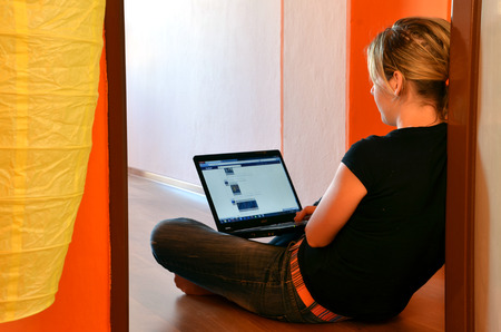 browses: Bytca, Slovakia - April 27, 2012: Young woman browses her facebook page on laptop seated on the floor