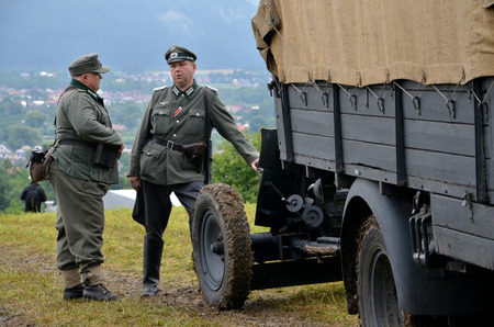 reenaction: Strecno, Slovakia - July 21, 2012: Historic truck with two men dressed in german nazi uniforms during historical reenactment of World War 2 battle Editorial