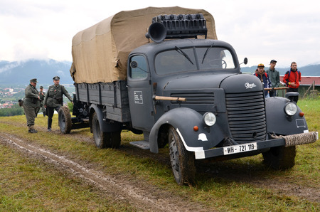 reenacting: Strecno, Slovakia - July 21, 2012: Historic truck with two men dressed in german nazi uniforms during historical reenactment of World War 2 battle Editorial