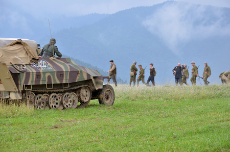 german fascist: Strecno, Slovakia - July 21, 2012: Historical reenactment of World War 2 battle - armored transport vehicle  and soldiers dressed in german nazi uniforms