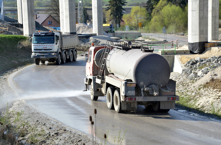 d1: Dolny Hricov, Slovakia - April 13, 2016: Water tanker splashes water on the road to prevent dust on work site. There is slovak highway labeled D1 under construction.