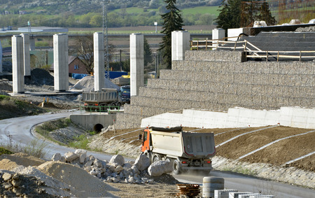sustained: Dolny Hricov, Slovakia - April 13, 2016: Slovak highway labeled D1 under construction. The work site with pillars, sustained wall and trucks driving on the road.