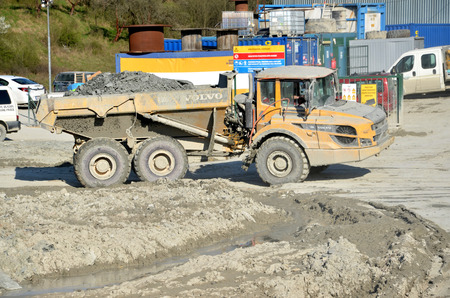 d1: Dolny Hricov, Slovakia - April 13, 2016: Dirty heavy Volvo dumper loaded by rock moving in work site. There is slovak highway labeled D1 under construction.