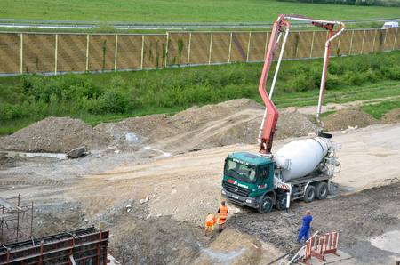 concrete pump: Dolny Hricov, Slovakia - May 20, 2016: Three workers and concrete transport truck with concrete pump ready for use. This activity is related to railway reconstruction process.