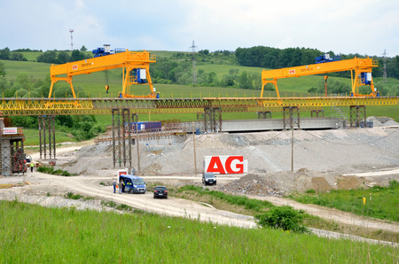 d1: Ovciarsko, Slovakia - May 27, 2016: Yellow bridge crane on construction site of slovak D1 highway. Except for the crane there are some workers and cars.