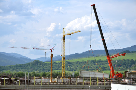 highway 3: Three high working cranes on highway construction site Stock Photo