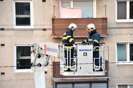 uprise: Bytca, Slovakia - June 4, 2016: Two firefighters uprise into telescopic boom basket of fire truck, block of flats in background