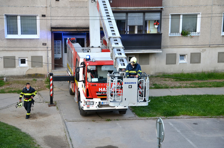 uprise: Bytca, Slovakia - June 4, 2016: Firefighter begin to uprise into telescopic boom basket of fire truck, block of flats in background