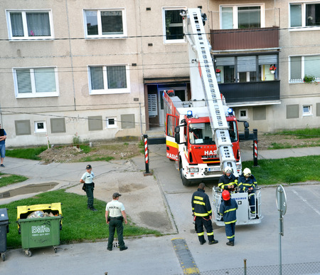 telescopic: Bytca, Slovakia - June 4, 2016: Firefighters in action, two of them get aboard into telescopic boom basket. Two police officers stand next to the fire truck