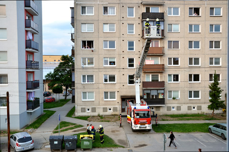uprise: Bytca, Slovakia - June 4, 2016: Firefighters in action, two men uprise in telescopic boom basket of fire truck. Some people are watching, block of flats in background. Editorial