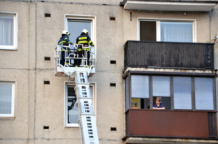 unafraid: Bytca, Slovakia - June 4, 2016: Two firefighters into telescopic boom basket of fire truck try to get to the flat balcony. Old woman is watching them from next balcony.