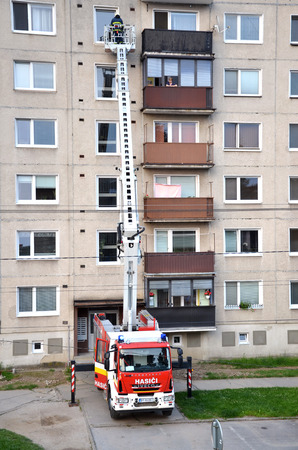 uprise: Bytca, Slovakia - June 4, 2016: Firefighters in action, a man uprise in telescopic boom basket of fire truck. Block of flats in background. Editorial