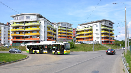 public houses: Zilina, Slovakia - June 4, 2016: Group of coloured apartment dwelling houses, on crossroad stopped new city bus, the part of urban public transportation. Editorial