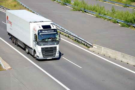 d1: Dolny Hricov, Slovakia - June 29, 2016: White moving Volvo truck coupled with semi-trailer located on slovak D1 highway.