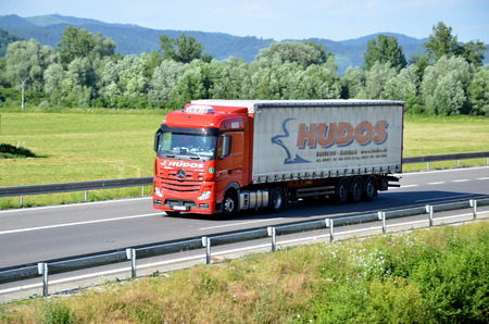 d1: Dolny Hricov, Slovakia - June 29, 2016: Red moving Mercedes-Benz Actros truck coupled with semi-trailer located on slovak D1 highway surrounded by green field and trees.
