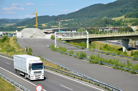 d1: Dolny Hricov, Slovakia - June 29, 2016: White MAN truck drives on slovak D1 highway. In background is new part of this way under construction. Editorial