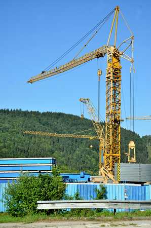 forested: Many standing yellow tower cranes, forested hill and blue sky in background