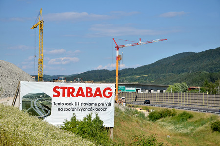d1: Dolny Hricov, Slovakia - June 29, 2016: Two tower cranes working on construction site of slovak D1 highway, billboard of Strabag building company in foreground (translation: We are building this section of D1 highway for you on solid footing)