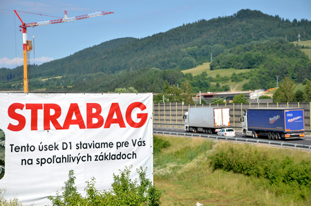 d1: Dolny Hricov, Slovakia - June 29, 2016: Tower crane working on construction site of slovak D1 highway, billboard of Strabag building company in foreground (translation: We are building this section of D1 highway for you on solid footing) Editorial