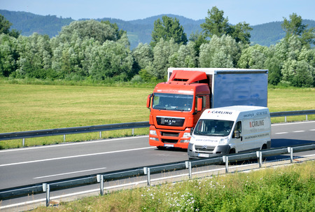 d1: Dolny Hricov, Slovakia - June 29, 2016: White Citroën van overtakes red MAN truck on slovak D1 highway in countryside. Editorial