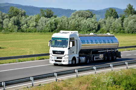 d1: Dolny Hricov, Slovakia - June 29, 2016: White MAN truck coupled with tank semi-trailer drived on slovak D1 highway in countryside.