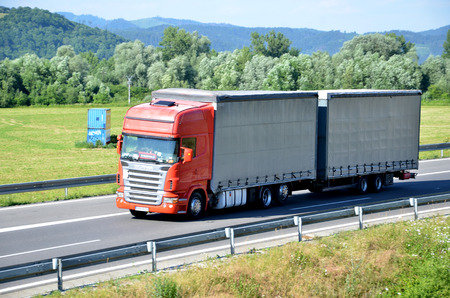 coupled: Dolny Hricov, Slovakia - June 29, 2016: Red Scania truck coupled with trailer drived on slovak D1 highway in countryside.