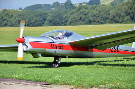 Ocova, Slovakia - August 2, 2014: Silver and red glider stands on grass landing strip in small country airport while the weather is nice