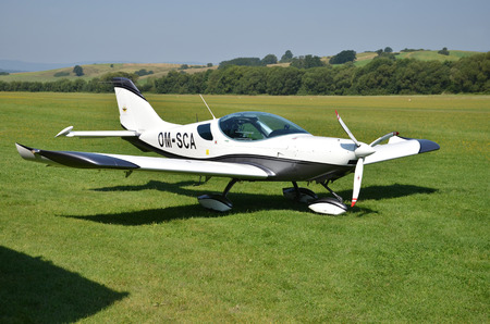 Ocova, Slovakia - August 2, 2014: Ultralight double-seat propeller-driven PS-28 Cruiser airplane stands on grass landing strip in small country airport