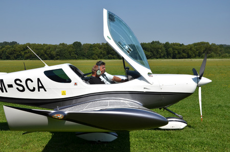 airplane ultralight: Ocova, Slovakia - August 2, 2014: Two men sit into ultralight propeller-driven airplane and get ready for taking off