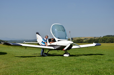airplane ultralight: Ocova, Slovakia - August 2, 2014: Men check the small personal airplane before taking off and prepare for the flight next to grass landing strip Editorial