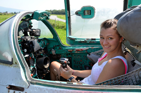 Ocova, Slovakia - August 2, 2014: Girl sits and smiles in cabin of old jet fighter MiG-21 holding the control stick Editorial