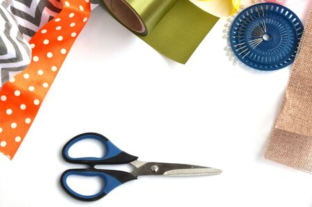 Flat lay made by color ribbons, scissors and pins on white background