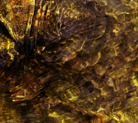 background of yellow colored ripples on water stream photo
